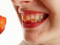 Θηλυκό στόμα με τα μούρα φραουλών δοντιών σε ένα άσπρο υπόβαθρο στοκ φωτογραφία