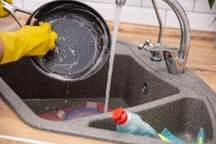 Θηλυκό τηγανίζοντας τηγάνι πλύσης χεριών Νέο ταψάκι πλύσης γυναικών νοικοκυρών σε έναν νεροχύτη κουζινών με ένα σφουγγάρι, καθαρι στοκ εικόνες