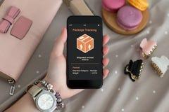 Θηλυκό τηλέφωνο εκμετάλλευσης χεριών με app την ακολουθώντας συσκευασία παράδοσης Στοκ εικόνες με δικαίωμα ελεύθερης χρήσης