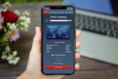 Θηλυκό τηλέφωνο εκμετάλλευσης χεριών με app τις σε απευθείας σύνδεση αγορές στην οθόνη Στοκ Εικόνες