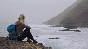 Θηλυκό τουριστών που θαυμάζει τα ισχυρά κύματα που καταβρέχουν στη δύσκολη ακτή Τεράστια ηφαιστειακά βουνά τραχιά στην οδοιπορία απόθεμα βίντεο