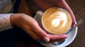 Θηλυκό φλυτζάνι καφέ λαβής χεριών με τη μορφή καρδιών στον ξύλινο πίνακα απόθεμα βίντεο