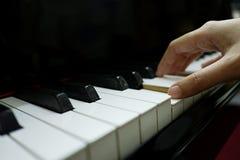 θηλυκό χέρι κινηματογραφήσεων σε πρώτο πλάνο που παίζει το μεγάλο πιάνο στοκ φωτογραφία