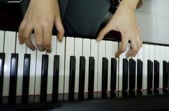 θηλυκό χέρι κινηματογραφήσεων σε πρώτο πλάνο που παίζει το μεγάλο πιάνο στοκ εικόνες