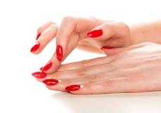 Θηλυκό χέρι με το κόκκινο μανικιούρ που εφαρμόζει την κρέμα στην επιδερμίδα στοκ εικόνες
