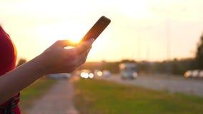 Θηλυκό χέρι με το smartphone ενάντια στην οδήγηση των αυτοκινήτων στο δρόμο φιλμ μικρού μήκους