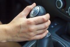 Θηλυκό χέρι οδηγών που μετατοπίζει το εργαλείο με το χέρι κορίτσι οδήγησης αυτοκ&i Στοκ Εικόνα