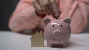 Θηλυκό χέρι που βάζει το νόμισμα στο piggybank, ξύλινο σπίτι παιχνιδιών που στέκεται πλησίον, υποθήκη απόθεμα βίντεο