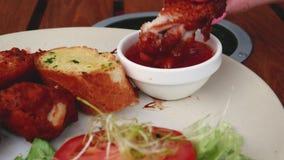 Θηλυκό χέρι που βυθίζει τα τηγανισμένα φτερά κοτόπουλου στη σάλτσα ντοματών, νόστιμο ανθυγειινό γεύμα απόθεμα βίντεο