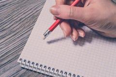 Θηλυκό χέρι που γράφει με το μολύβι και που χρησιμοποιεί τη γόμα στο σημειωματάριο στο γκρίζο ξύλινο υπόβαθρο Εκλεκτής ποιότητας  Στοκ Φωτογραφία