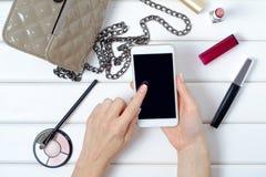 Θηλυκό χέρι που κρατά ένα καλλυντικό κινητό τηλεφωνικό smartphone τσαντών Στοκ φωτογραφία με δικαίωμα ελεύθερης χρήσης