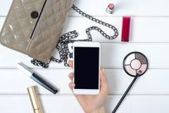 Θηλυκό χέρι που κρατά ένα καλλυντικό κινητό τηλεφωνικό smartphone τσαντών Στοκ εικόνα με δικαίωμα ελεύθερης χρήσης