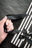 Θηλυκό χέρι που κρατά μια συσκευασία στα άσπρα και μαύρα λωρίδες με μια κινηματογράφηση σε πρώτο πλάνο τόξων Στοκ Φωτογραφίες