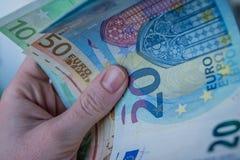 Θηλυκό χέρι που κρατά τα ευρο- τραπεζογραμμάτια στοκ φωτογραφία με δικαίωμα ελεύθερης χρήσης