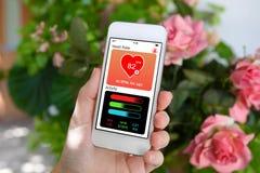 Θηλυκό χέρι που κρατά το άσπρο τηλεφωνικό app SCR δραστηριότητας υγείας ακολουθώντας Στοκ Εικόνες