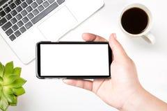 Θηλυκό χέρι που κρατά το κινητό έξυπνο τηλέφωνο με την κενή άσπρη οθόνη ενάντια στο σύγχρονο lap-top, τον καφέ και τις πράσινες ε στοκ φωτογραφίες με δικαίωμα ελεύθερης χρήσης