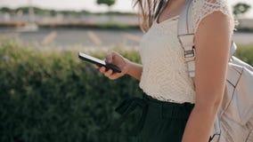 Θηλυκό χέρι που κρατά το κινητό τηλέφωνο στο υπόβαθρο της παλαιάς πόλης το καλοκαίρι, κινηματογράφηση σε πρώτο πλάνο απόθεμα βίντεο