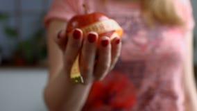 Θηλυκό χέρι που κρατά το κόκκινο μήλο με τη μέτρηση της ταινίας απόθεμα βίντεο