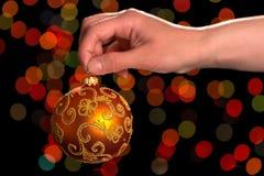 Θηλυκό χέρι που κρατά το όμορφο παιχνίδι σφαιρών Χριστουγέννων, που λαμπυρίζει στο σκοτάδι Στοκ Φωτογραφία