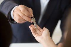 Θηλυκό χέρι που παίρνει το κλειδί από το realtor που αγοράζει νοικιάζοντας το νέο σπίτι Στοκ Φωτογραφίες