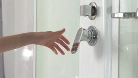 Θηλυκό χέρι που χρησιμοποιεί τη βρύση λουτρών στην καμπίνα ντους Κινηματογράφηση σε πρώτο πλάνο ενός ρυθμιστή εξογκωμάτων ντους κ απόθεμα βίντεο