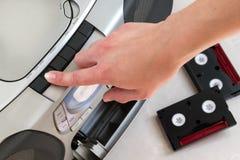 Θηλυκό χέρι που ωθεί το ανοικτό κουμπί σε ένα γκρίζο κέντρο μουσικής με δύο μαύρες και κόκκινες κασέτες στοκ φωτογραφία