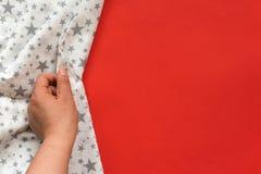 Θηλυκό χέρι σχετικά με το άσπρο ύφασμα στο κόκκινο υπόβαθρο Με το διάστημα αντιγράφων Στοκ φωτογραφία με δικαίωμα ελεύθερης χρήσης