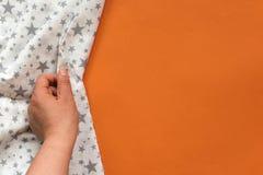 Θηλυκό χέρι σχετικά με το άσπρο ύφασμα στο πορτοκαλί υπόβαθρο Με το διάστημα αντιγράφων Στοκ Φωτογραφίες
