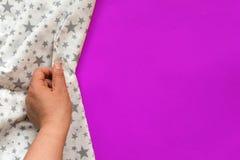 Θηλυκό χέρι σχετικά με το άσπρο ύφασμα στο πορφυρό υπόβαθρο Με το διάστημα αντιγράφων Στοκ φωτογραφίες με δικαίωμα ελεύθερης χρήσης