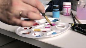 Θηλυκό χέρι dunks η βούρτσα στην μπλε παλέτα χρωμάτων απεικόνιση αποθεμάτων
