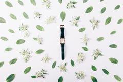 Θηλυκό χρυσό ρολόι μεταξύ των πράσινων λουλουδιών και των φύλλων Στοκ Φωτογραφία