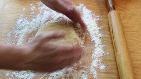 Θηλυκό ψεκασμένο χέρια αλεύρι σε έναν ξύλινο πίνακα και μια ζυμωμένη ζύμη απόθεμα βίντεο