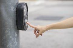 Θηλυκό ωθώντας κουμπί χεριών για το φωτεινό σηματοδότη Στοκ Εικόνες