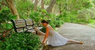 Θηλυκό ballerina που κάνει την τεντώνοντας άσκηση στο πάρκο 4k φιλμ μικρού μήκους