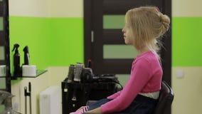 Θηλυκό hairstylist που καρφώνει επάνω την τρίχα που χρησιμοποιεί τη πόρπη μαλλιών απόθεμα βίντεο