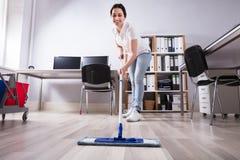 Θηλυκό Janitor καθαρίζοντας πάτωμα στην αρχή στοκ εικόνες