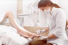 Θηλυκό podiatrist Brunette που κάνει τη στιλβωτική ουσία και τη διαδικασία καθαρισμού Στοκ φωτογραφία με δικαίωμα ελεύθερης χρήσης