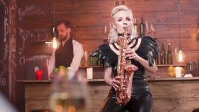Θηλυκό saxophonist που εκτελεί ένα τραγούδι μπροστά από ένα ακροατήριο φιλμ μικρού μήκους