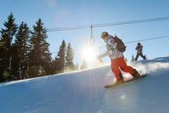 Θηλυκό snowboarder ενάντια στον ήλιο Στοκ φωτογραφία με δικαίωμα ελεύθερης χρήσης