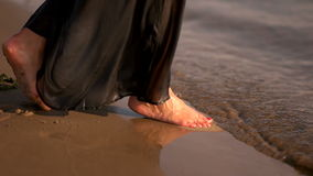 Θηλυκά πόδια γυναικών χωρίς παπούτσια στην παραλία άμμου μέσα στο νερό φιλμ μικρού μήκους