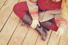 Θηλυκά πόδια που ντύνονται στα παπούτσια δέρματος με τις δαντέλλες και τις πλεκτές γυναικείες κάλτσες στοκ φωτογραφία με δικαίωμα ελεύθερης χρήσης
