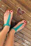 Θηλυκά πόδια που φορούν τα τυρκουάζ σανδάλια Στοκ Εικόνες