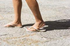 Θηλυκά πόδια που φορούν τις άσπρες σαγιονάρες στοκ φωτογραφία