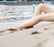 Θηλυκά πόδια σε ένα υπόβαθρο ποταμών στοκ εικόνα