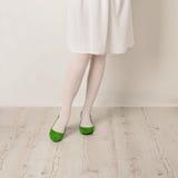 Θηλυκά πόδια στα άσπρα καλσόν, επίπεδα φουστών και μπαλέτου σε ένα άσπρο β Στοκ φωτογραφίες με δικαίωμα ελεύθερης χρήσης
