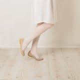Θηλυκά πόδια στα άσπρα καλσόν, επίπεδα φουστών και μπαλέτου σε ένα άσπρο β Στοκ Φωτογραφία