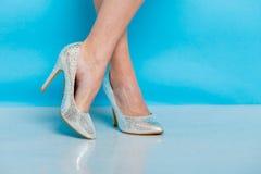 Θηλυκά πόδια στα ασημένια υψηλά παπούτσια τακουνιών Στοκ Εικόνες