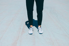 Θηλυκά πόδια στα μαύρα εσώρουχα και πάνινα παπούτσια σε ένα μπλε συγκεκριμένο δικαστήριο στοκ φωτογραφία με δικαίωμα ελεύθερης χρήσης
