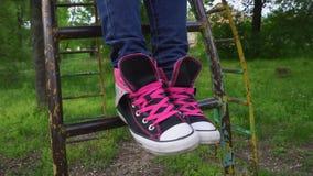 Θηλυκά πόδια στα πάνινα παπούτσια που κινούν και που θέτουν την άνοιξη το πάρκο απόθεμα βίντεο