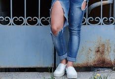 Θηλυκά πόδια στα σχισμένα τζιν, κινηματογράφηση σε πρώτο πλάνο, στα πλαίσια του δικτυωτού δικτυωτού πλέγματος Στοκ Εικόνες